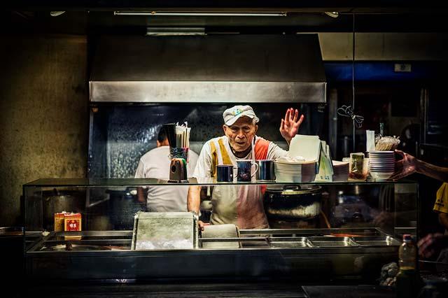 Fotografía urbana nocturna hombre saludando a la cámara
